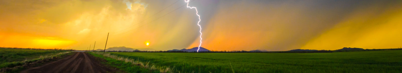 lightning striking, green grass foreground and orange sky background. Image by Dwayne Kear