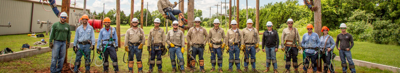 Banner image of Oklahoma Electric Cooperative Linemen in full gear, in front of power poles