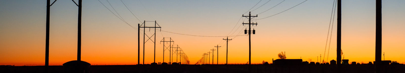 row of powerlines at sunset, sky from blue to orange